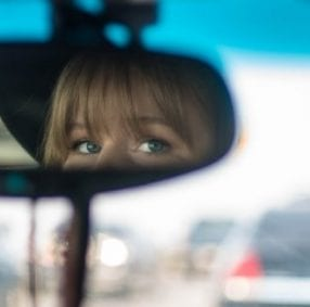 Lady looking in rear-view mirror